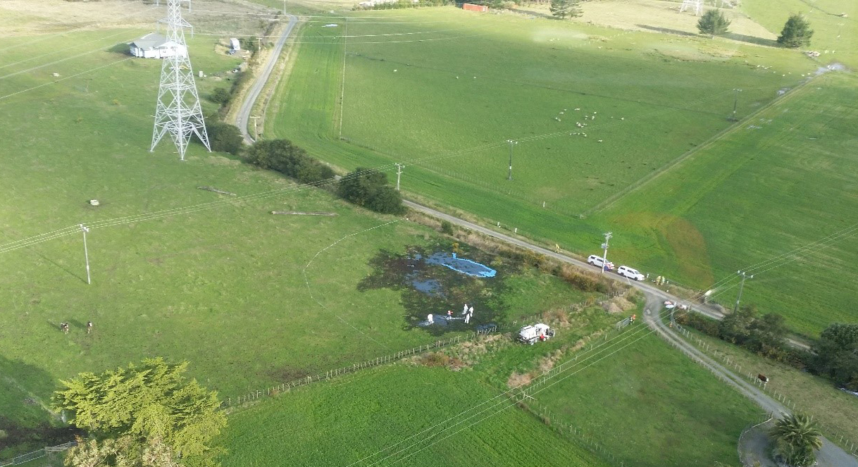Aerial photographs showing investigation work at the site of the leak. This is the same field from Figure 4 and in the same area which appeared to have had earthworks completed. The pylon, road, and house are all visible as landmarks. There is a large area where the fuel has soaked the ground causing it to turn a black colour. In some areas a neon blue liquid has formed pools, this appears to be areas with a higher concentration of jet fuel.